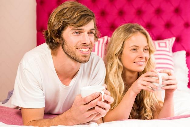 Joli couple se reposant sur leur lit et prenant un café dans leur chambre