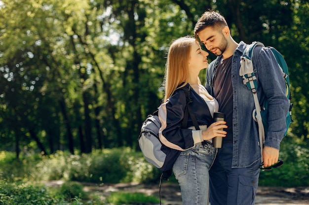 Joli couple se reposer dans une forêt en été