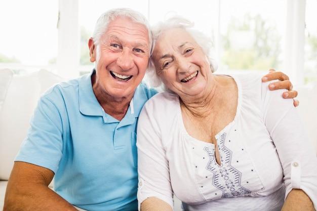 Joli couple senior souriant assis sur un canapé
