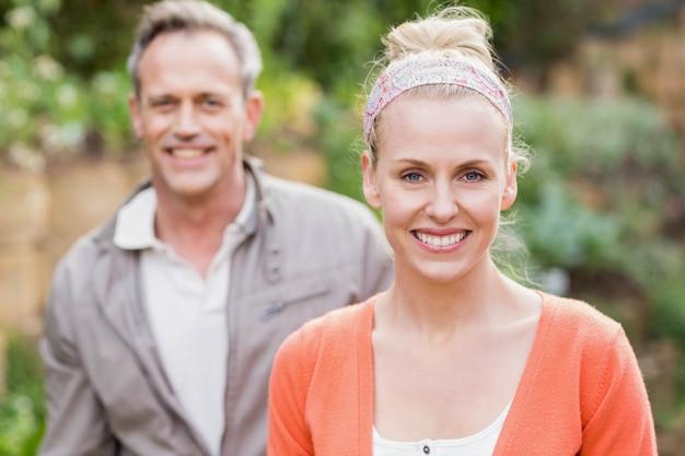 Joli couple souriant à la caméra dans le jardin