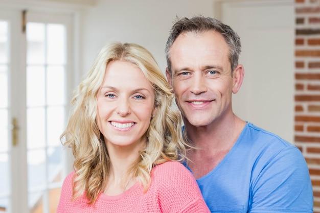 Joli couple souriant à la caméra dans le salon