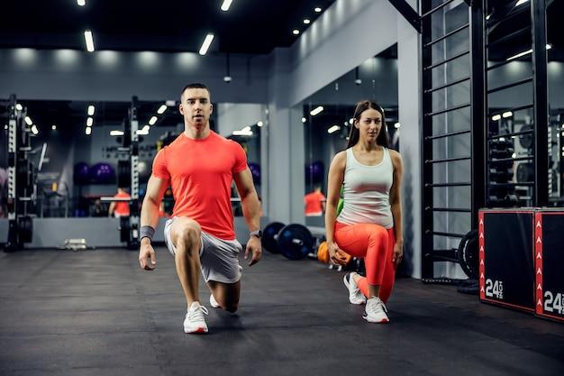 Un joli couple sportif exerçant des pas en avant pour les jambes et les fesses sur un sol noir dans une salle de sport intérieure avec un miroir. fitness et mode de vie sportif