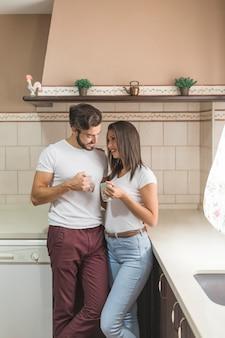 Joli couple avec des tasses sur une cuisine élégante