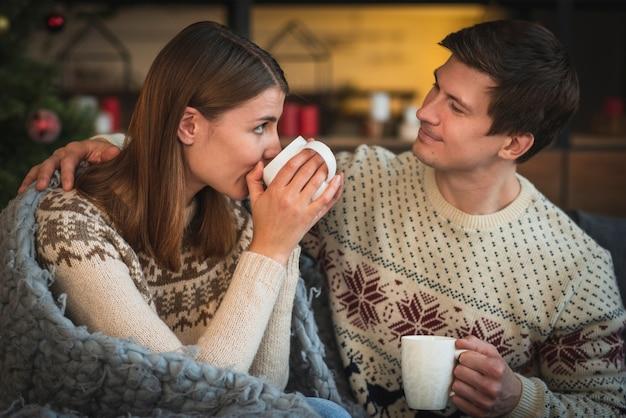 Joli couple tenant des boissons chaudes