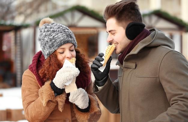 Joli couple en train de déjeuner sur le marché d'hiver
