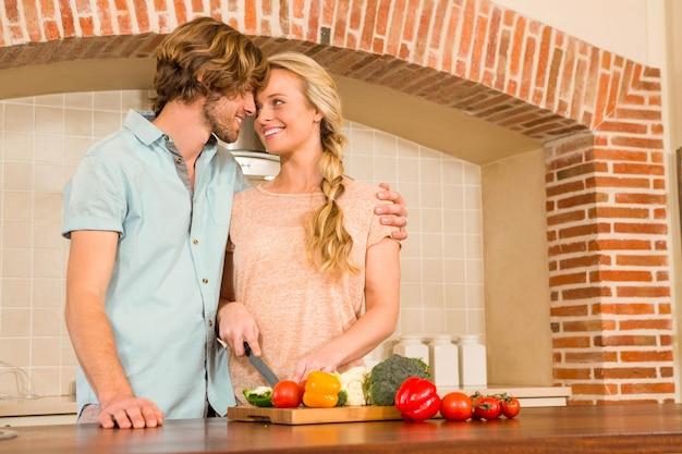 Joli couple trancher des légumes dans la cuisine