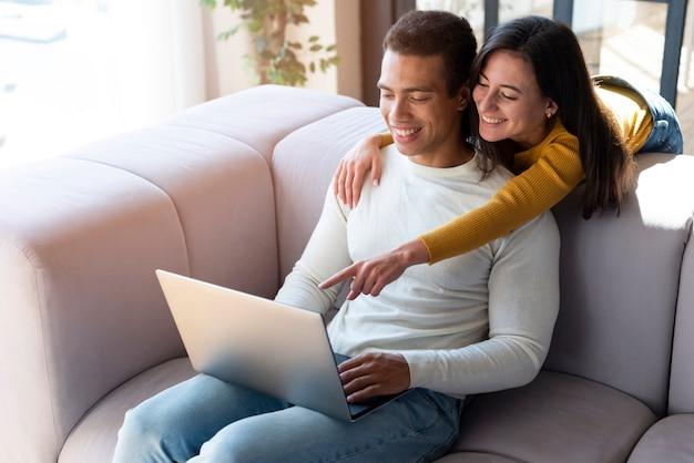 Joli couple utilisant un ordinateur portable ensemble