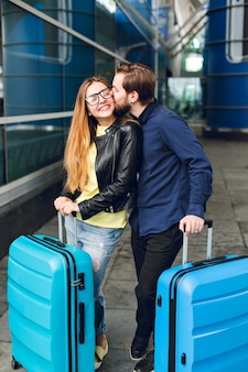 Joli couple avec des valises est debout à l'extérieur de l'aéroport. elle a les cheveux longs, des lunettes, un pull jaune, une veste. il porte une chemise noire, une barbe. guy étreint et embrasse la fille.