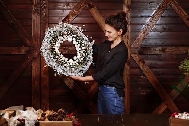 Joli designer souriant montrant la guirlande de noël à feuilles persistantes. jeune femme tenant une guirlande de noël.
