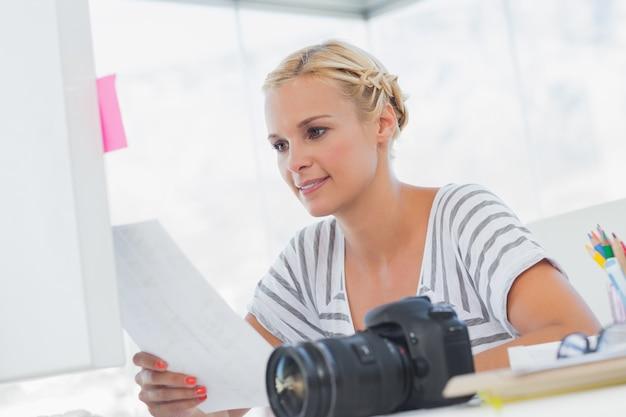 Joli éditeur de photos en regardant une fiche contact