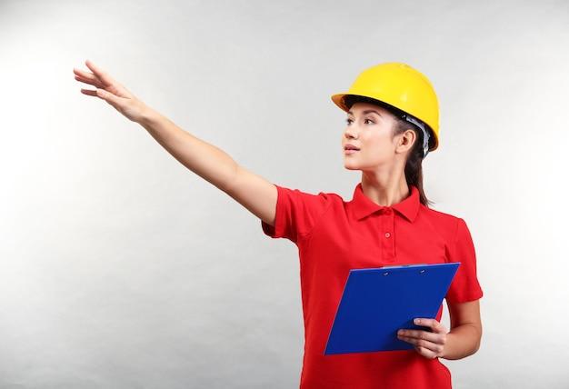 Joli employé d'entrepôt avec presse-papiers pointant vers quelque chose