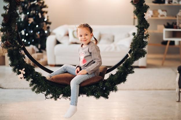 Joli enfant assis sur une balançoire de noël.