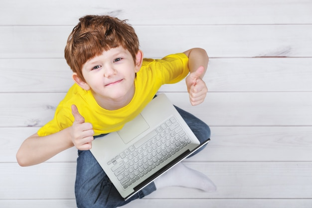 Joli enfant montrant les pouces vers le haut et jouant sur un ordinateur portable sur un sol en stratifié ou en parquet chaud.