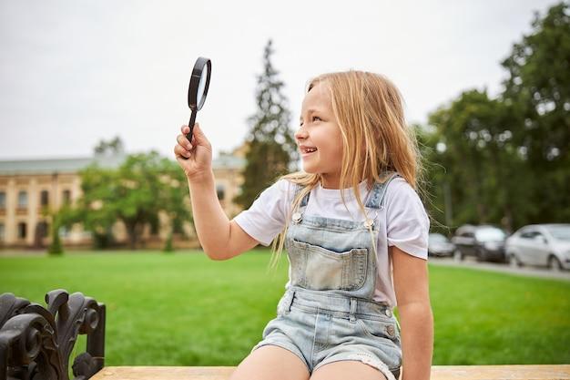 Joli enfant regardant à travers la loupe vers le ciel tout en étant assis sur le banc en bois dans le parc