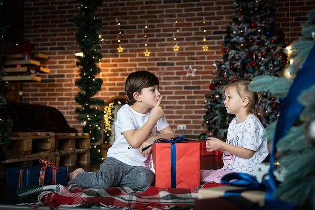 Un joli frère et sœur en pyjama racontant des secrets à côté d'un arbre de noël dans une pièce décorée