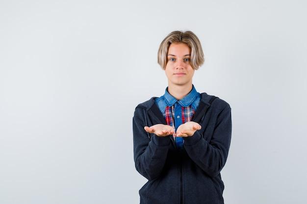 Joli garçon adolescent en chemise, sweat à capuche montrant un geste de réception ou de geste et l'air doux, vue de face.
