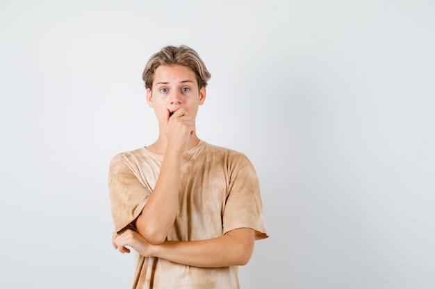 Joli garçon adolescent gardant la main sur la bouche en t-shirt et ayant l'air troublé, vue de face.