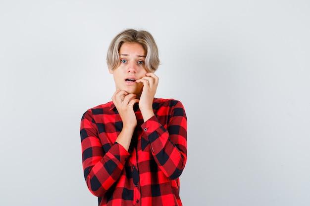 Joli garçon adolescent avec la main sur la joue en chemise à carreaux et l'air terrifié, vue de face.
