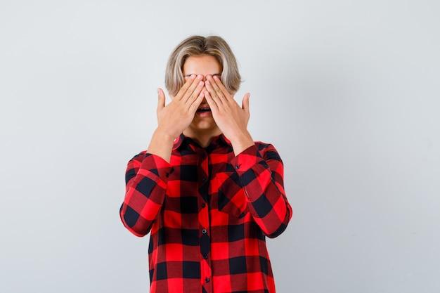 Joli garçon adolescent avec les mains sur les yeux en chemise à carreaux et l'air excité, vue de face.