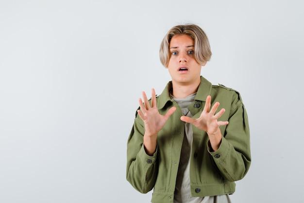 Joli garçon adolescent montrant un geste d'abandon en veste verte et ayant l'air effrayé