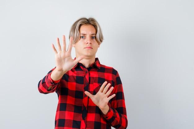 Joli garçon adolescent montrant un geste d'arrêt en chemise à carreaux et ayant l'air effrayé. vue de face.