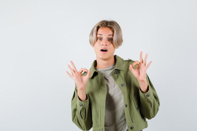 Joli garçon adolescent montrant un geste correct en veste verte et se demandant. vue de face.