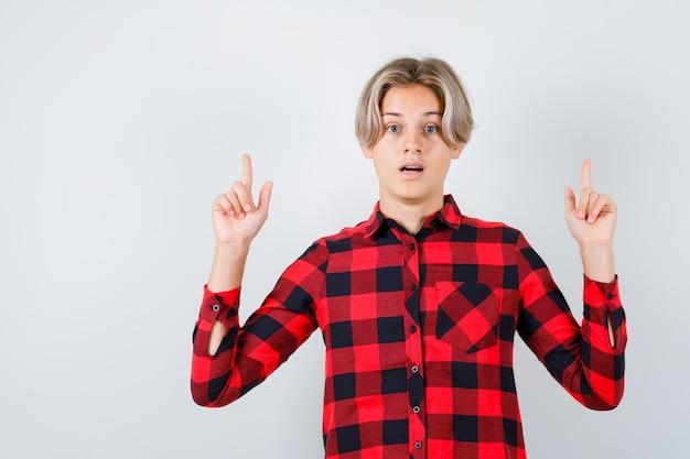Joli garçon adolescent pointant vers le haut en chemise à carreaux et l'air surpris, vue de face.