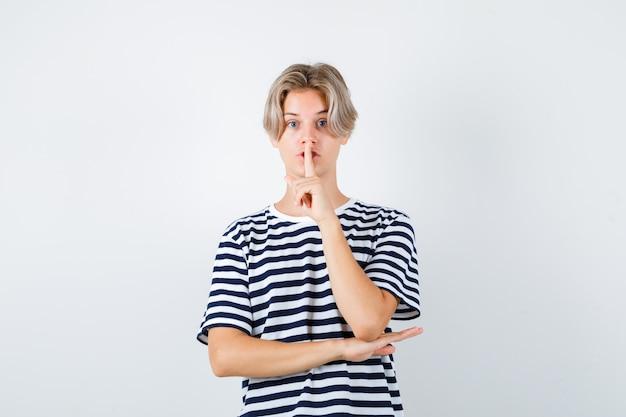 Joli garçon adolescent en t-shirt rayé montrant un geste de silence et ayant l'air effrayé, vue de face.
