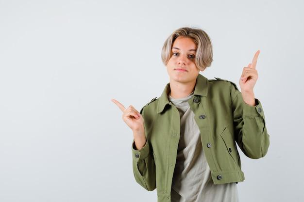 Joli garçon adolescent en veste verte pointant vers le haut et à la recherche d'hésitant