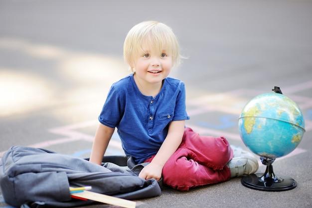 Joli garçon blond fait ses devoirs assis sur cour d'école après l'école avec des sacs pose à proximité.