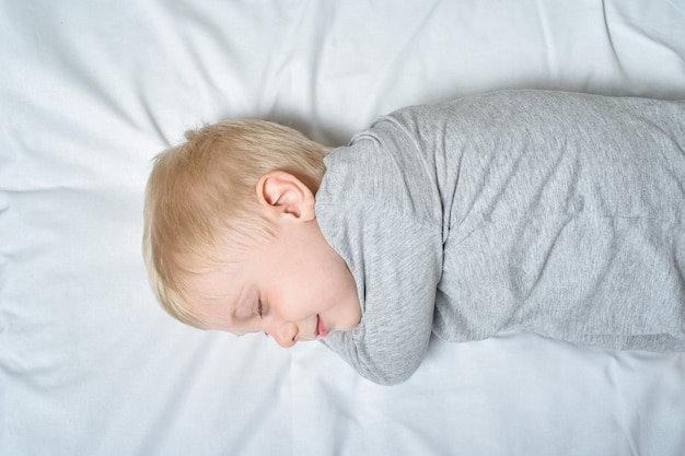 Joli garçon blond qui dort la main sous la tête.