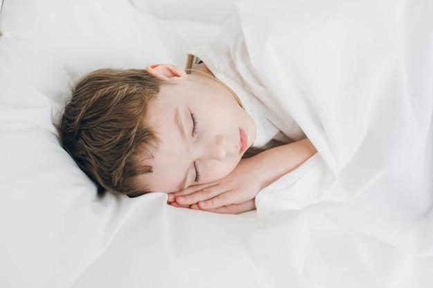 Joli garçon dort le matin au lit
