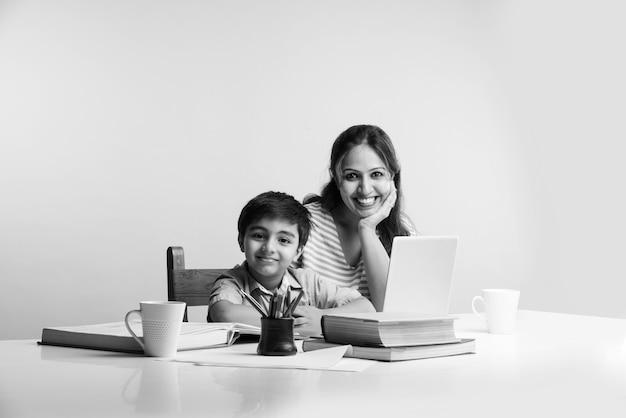 Joli garçon indien avec sa mère faisant ses devoirs à la maison à l'aide d'un ordinateur portable et de livres - concept de scolarisation en ligne