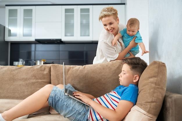 Joli garçon jouant sur un ordinateur portable pendant que la mère porte bébé