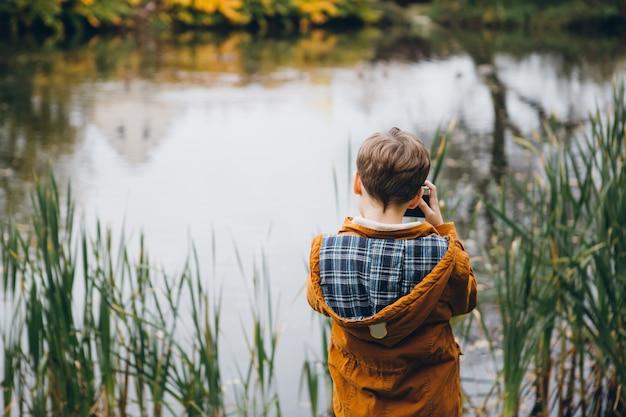 Joli garçon marche et pose dans un parc d'automne coloré