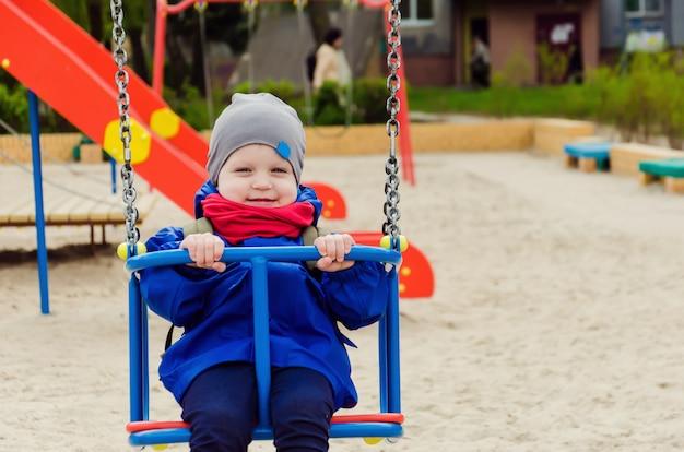 Joli garçon mignon de deux ans dans une veste bleue et une écharpe rouge joue dans une aire de jeux pour enfants lumineuse
