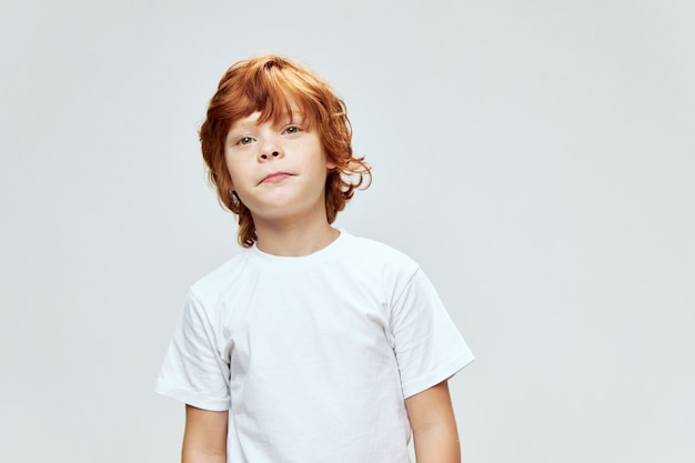 Joli garçon rousse en t-shirt blanc a l'air droit vue recadrée studio