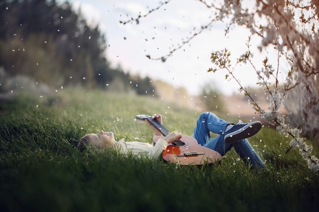 Joli garçon se trouve sur l'herbe avec une guitare au coucher du soleil