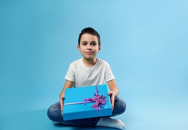 Joli garçon souriant posant avec un cadeau d'anniversaire dans ses mains sur une surface bleue avec espace copie