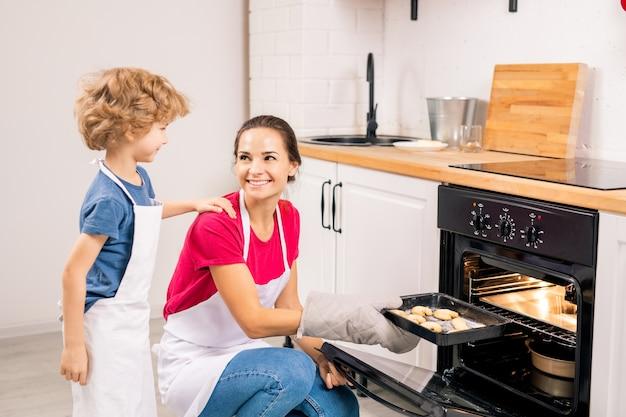 Joli garçon en tablier parlant à sa maman mettant le plateau avec des biscuits crus dans le four pendant la cuisson ensemble dans la cuisine
