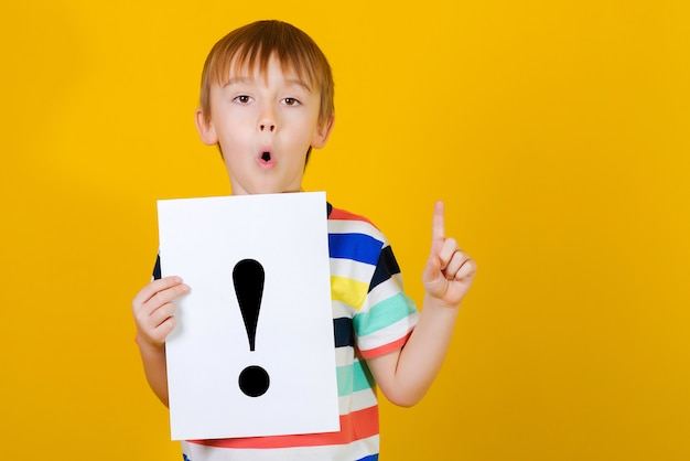 Joli garçon tenant une feuille de papier avec un point d'exclamation