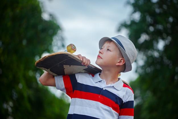 Joli garçon tenant la planche à roulettes à la main à l'extérieur. casquette et vêtements élégants