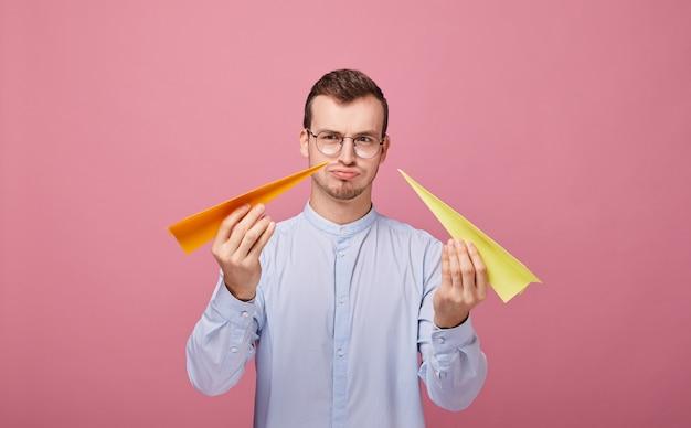 Un joli homme bien élevé aux cheveux noirs avec deux avions en papier dans ses mains