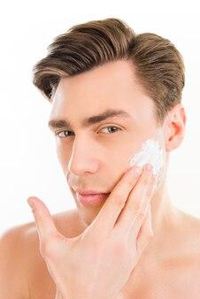Joli homme enduisant de mousse sur son visage