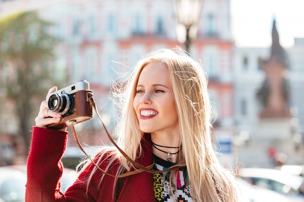 Joli, jeune, caucasien, marche femme, dehors, tenue, appareil photo