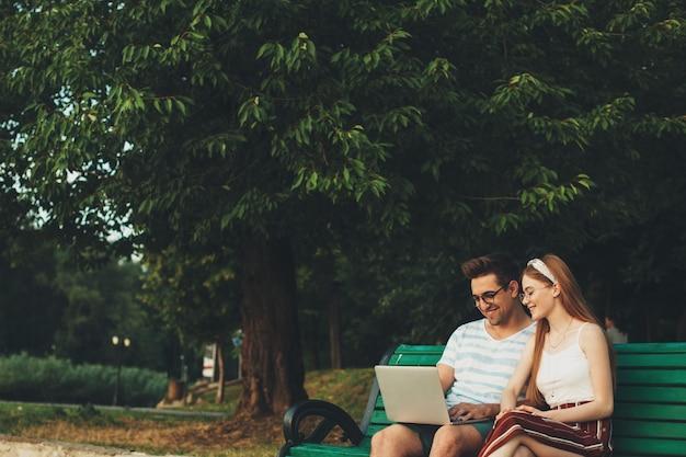 Joli jeune couple assis sur un banc dans le parc à la recherche d'un ordinateur portable en riant contre un arbre.