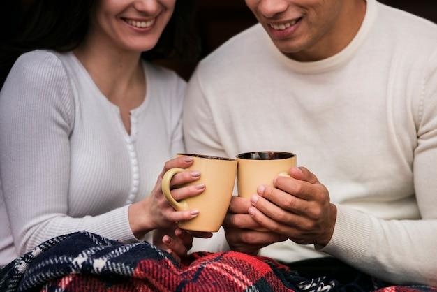 Joli jeune couple avec boissons chaudes