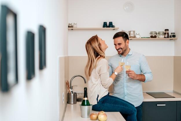 Joli jeune couple buvant du vin en cuisine.