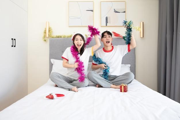 Joli jeune couple célébrant noël sur le lit