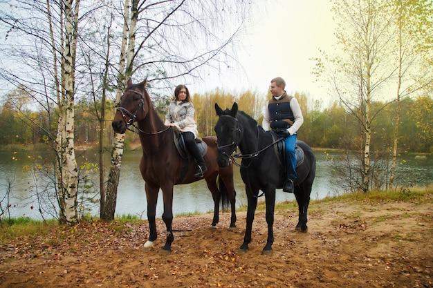 Joli jeune couple à cheval dans la forêt d'automne au bord du lac. cavaliers en automne park par mauvais temps nuageux avec pluie légère. concept d'équitation en plein air, de sports et de loisirs. espace de copie
